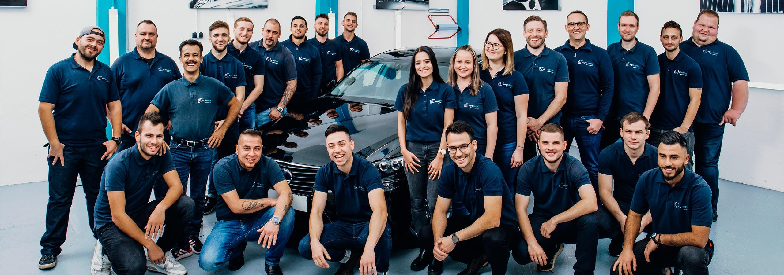Team AutOptik, 24 Mitarbeiter/-innen vor und neben schwarzem Audi, Autoaufbereitung Bayreuth, Bamberg, Hof.