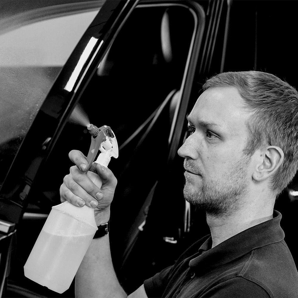 AutOptik-Mitarbeiter reinigt Fensterscheibe von Auto während des Firmeservices für Autohäuser
