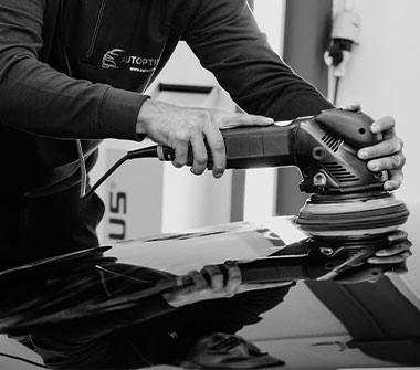 AutOptik-Mitarbeiter poliert Motorhaube von Auto, Carnaubawachs, Lackversiegelung Bayreuth, Bamberg, Hof.