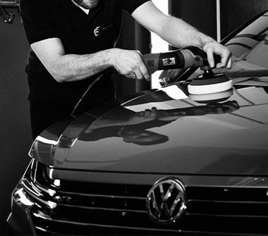 AutOptik-Mitarbeiter poliert Motorhaube von VW, Nano-Lackversiegelung Bayreuth, Bamberg, Hof.