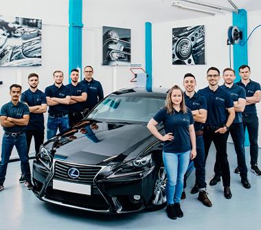 Team AutOptik in Bayreuth, eine Mitarbeiterin und neun Mitarbeiter neben schwarzem Auto, Autoaufbereitung Bayreuth.