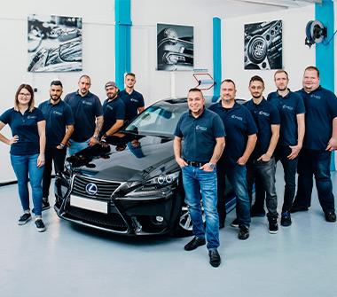 Team AutOptik in Hof, eine Mitarbeiterin und neun Mitarbeiter neben schwarzem Auto, Autoaufbereitung Hof.