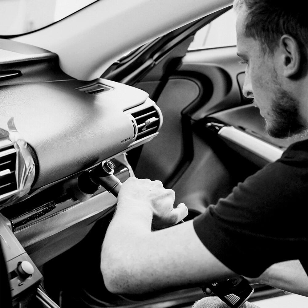 AutOptik-Mitarbeiter beim Reinigen des Innenraums eines Autos während des Firmenservices für Versicherungen.