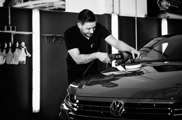 AutOptik-Mitarbeiter poliert Motorhaube von VW, Fahrzeugaufbereitung und Lackversiegelung Bamberg, Bayreuth, Hof.
